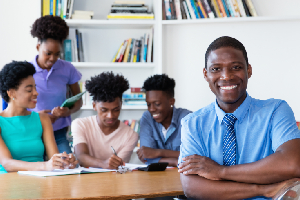 Handsome African male teacher with class at classroom of school